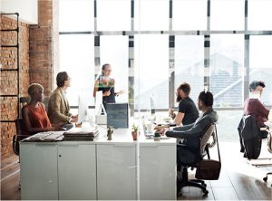 Four people sitting around a square table that has folders and computers on it. Behind the table a woman is standing pointing towards the table, behind the woman are windows. - TAB Bank