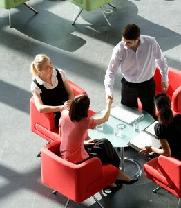 Four people sitting in chairs around a small circle table. The person on the far right is standing and shaking the hand of the person who is on the far left. - TAB Bank