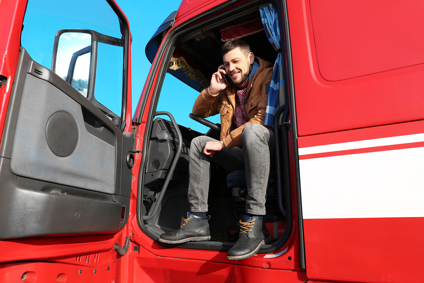 Man sitting on the driver's side of a semi-truck with the door open while holding his phone to his ear. - TAB Bank